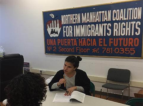 Woman sitting at a table teaching other people and behind her is the sign for the Northern Manhattan Coalition for Immigrants Rights.
