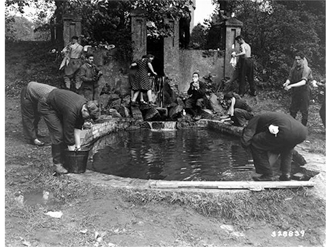 Image of Jewish Displaced Persons wash up in a pool at a displaced persons camp near Hagenow, Germany, May 30, 1945. *United States Holocaust Memorial Museum, courtesy of National Archives and Records Administration, College Park.