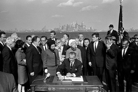 Image of President Lyndon B. Johnson signs the Immigration and Nationality Act as Vice President Hubert Humphrey, Lady Bird Johnson, Muriel Humphrey, Sen. Edward (Ted) Kennedy, Sen. Robert F. Kennedy, and others look on. *LBJ Presidential Library.