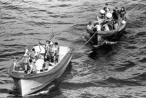 Image of A life boat from the USS BLUE RIDGE (LCC 19) tows a Vietnamese fishing boat to the amphibious command ship. 35 Vietnamese refugees were rescued 350 miles north of Cam Ranh Bay, Vietnam, after spending eight days at sea, May 15, 1984. *National Archives.