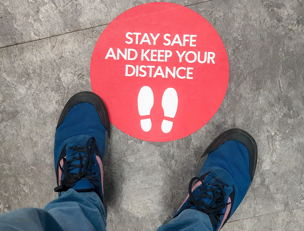 Image showing feet standing in front of a red circle that tells the person to stay safe and keep your distance.