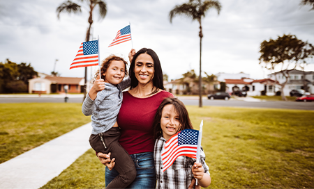 Woman and two young children standing outside waving American Flags
