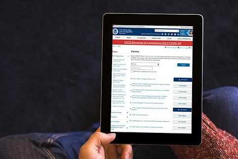 Picture of a person holding a tablet with a list of USCIS forms on the screen