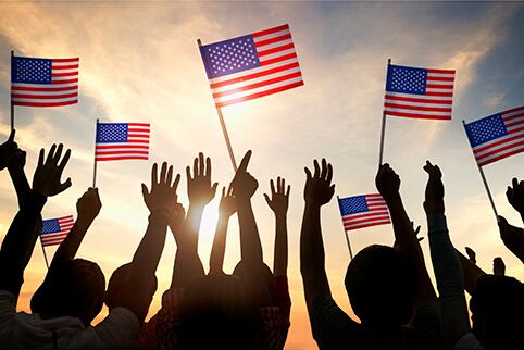 People with hands up waving American flags
