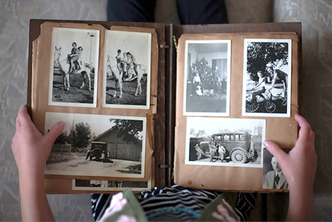 Photo album of old photos open on a person's lap.