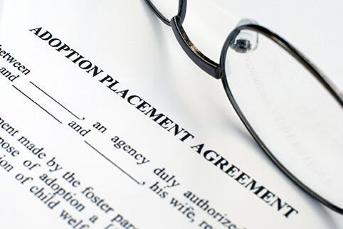 Paper with adoption  Placement agreement text and a pair of glasses laying on the paper