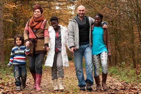 Family walking through the forest in fall