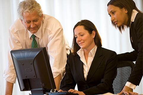 Two women and a man looking at a computer monitor