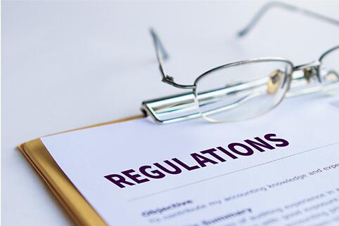 Clipboard with a paper on it that says Regulations. A pair of glasses are sitting on the clipboard.