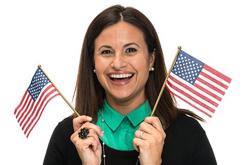 Woman holding an American Flag in each hand and smiling