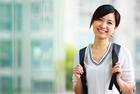 Woman standing smiling at camera wearing a backpack
