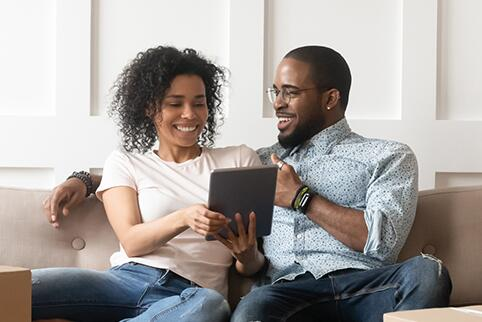 picture of a man and a woman sitting on a couch looking at a tablet