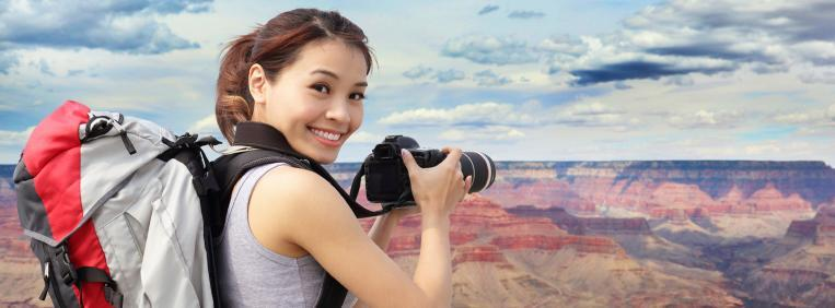 Woman with a backpack and a camera takes a picture of the Grand Canyon